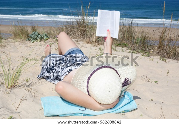 Woman reading book relaxed on the sand lying