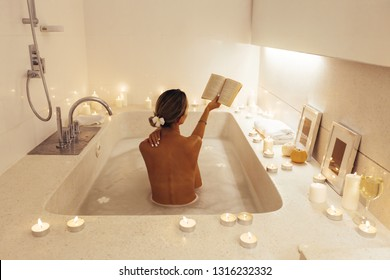 Woman reading book and relaxing in luxury spa bath decorated with candles. Spending romantic evening or night in bathroom.