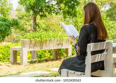 Woman is reading a book. She is sitting on a chair in a garden.