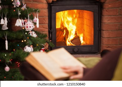 Woman reading a book sitting by the fireplace in the holidays season - focus on fire