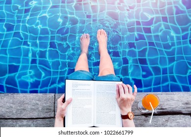 Woman Reading Book at the Swimming Pool Side, Relaxing with Summer Drink in her Vacation, Top View