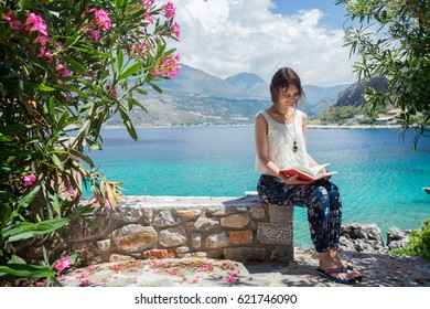 Woman reading a book while being on vacation. Travel and beauty lifestyle. Peloponnese, Limeni, Greece.