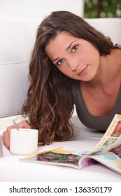 Woman reading a book while drinking a cup of tea