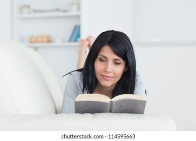 Woman reading a book while lying on a couch in a living room
