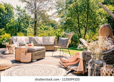 Woman reading book while relaxing at terrace with rattan furniture in the garden. Real photo