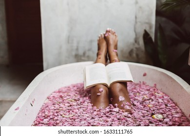 Woman reading book while relaxing in bath tub with flower petals, POV. Organic spa relaxation in luxury Bali outdoor bath.