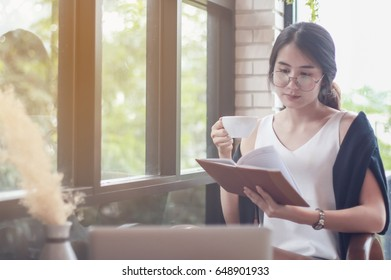 woman reading a book at the wooden counter desk in coffee shop with smile face in happy motion on blurred coffee shop view background under window light