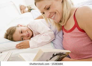 Woman reading book to young girl in bed smiling