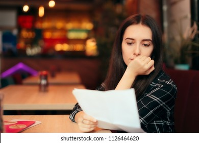Woman Reading Documents in a Coffee Shop. Girl analyzing a contract after just signing it
