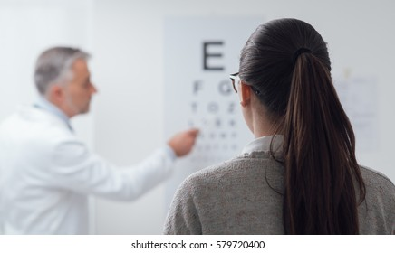 Woman reading the eye chart, the ophthalmologist is pointing at one letter and examing the patient, eye care concept