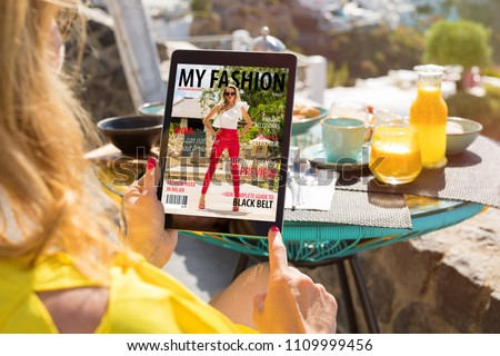 Woman reading fashion magazine on digital tablet. All contents are made up.