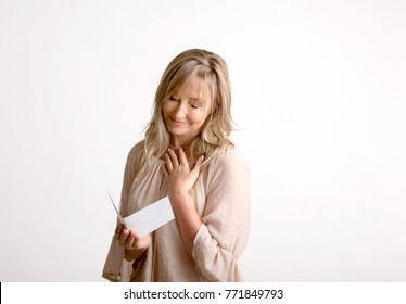 Woman reading a heartfelt message, note, book or card.   She is smiling and has her hand to heart. White background