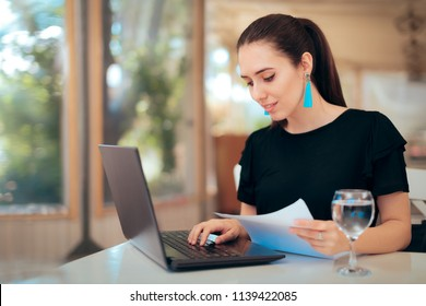 Woman Reading an Important Document while Typing on Laptop. Busy businesswoman analyzing paper documents