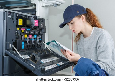 Woman reading instruction manual for photocopier