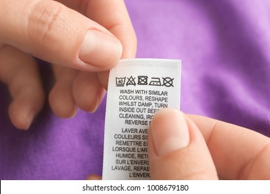 Woman reading instruction on clothing label, closeup