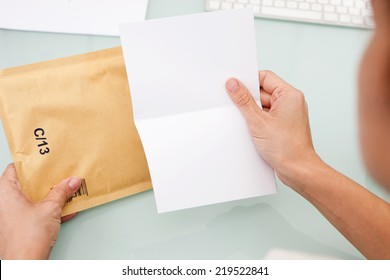 Woman reading letter. Blank card and envelope over grey background