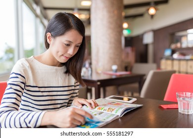 Woman reading magazine in cafe