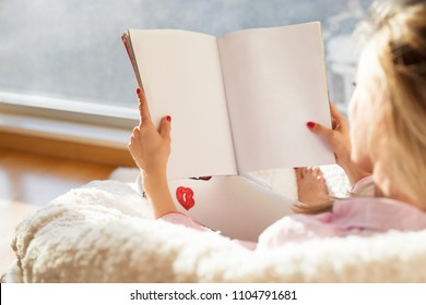 Woman reading magazine with empty white blank pages. Mockup and template for your own content.
