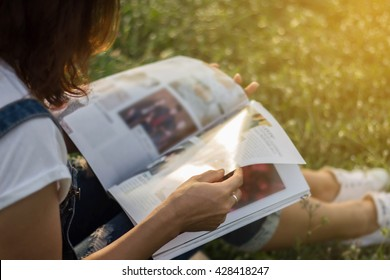 Woman reading a magazine in garden.
