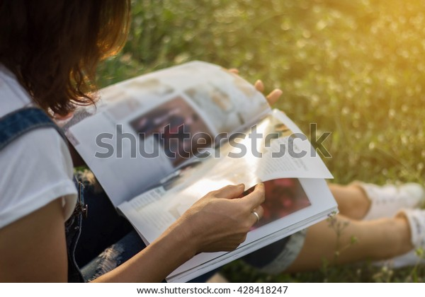 Woman reading a magazine in garden.