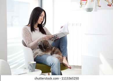 Woman reading magazine and relax with her dog
