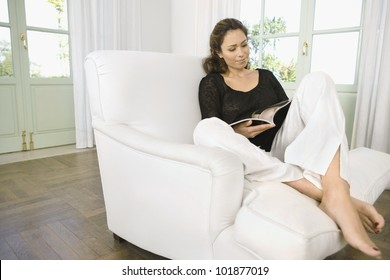 Woman reading a magazine while sitting on an armchair at home.