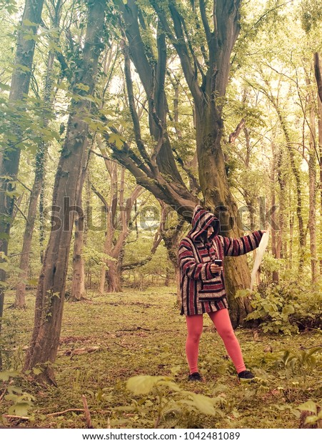 Woman reading map in lush green forest