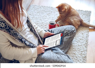 Woman reading news on tablet with cup of coffee. Online education concept. e-Learning