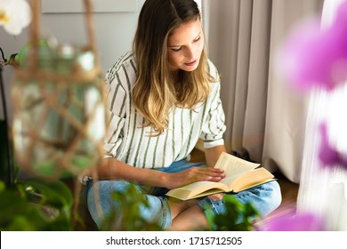 woman reading next to a bright window, relaxing and chilling during the outbreak period. Home activity for healthy mind