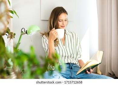 Frau, die neben einem hellen Fenster liest, entspannend, Kaffee trinken und Kälte während der Ausbruchszeit. Heimangebot für gesunden Geist