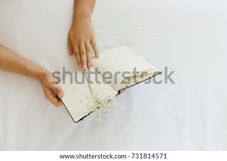 Woman is reading note book on the bedsheets