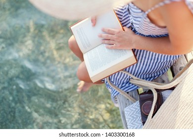Woman is reading paper book on wooden pier at sea beach. Girl is enjoying summer vacation and traveling. Tourist in straw hat is relaxing in holidays.