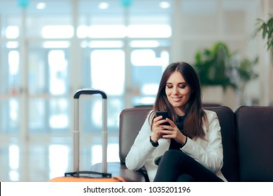 Woman Reading Phone Messages in Airport Waiting Room. Happy girl buying e-ticket, making hotel reservations and checking in online