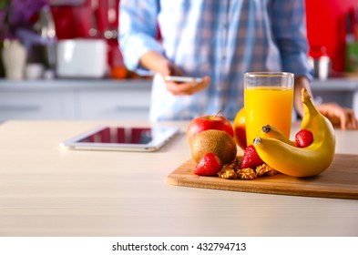 Woman reading recipe from phone in the kitchen