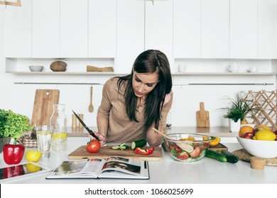 Woman reading recipe for simple summer salad in cookbook. Simple healthy food concept