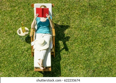 woman reading and relaxing in summer garden on lawn