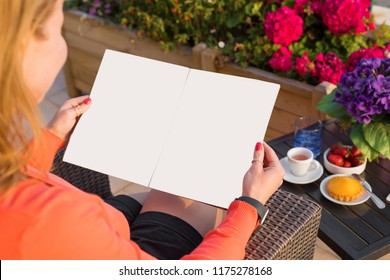 Woman reading sample magazine, empty mockup for your own design.