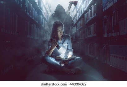 Woman reads a book in dark library