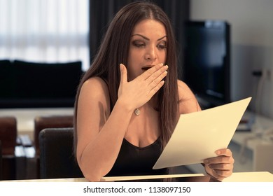 A woman reads negative news in a letter at home at a writing desk. The news of getting out of work. Subpoena. An agitated girl without joy. Emotions