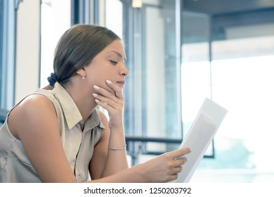Woman reads negative news in a letter at home on the couch. The shaken business manager of received a notice of dismissal from the company, surprised. An agitated girl without joy.