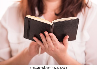 woman reads small black notebook - colse up