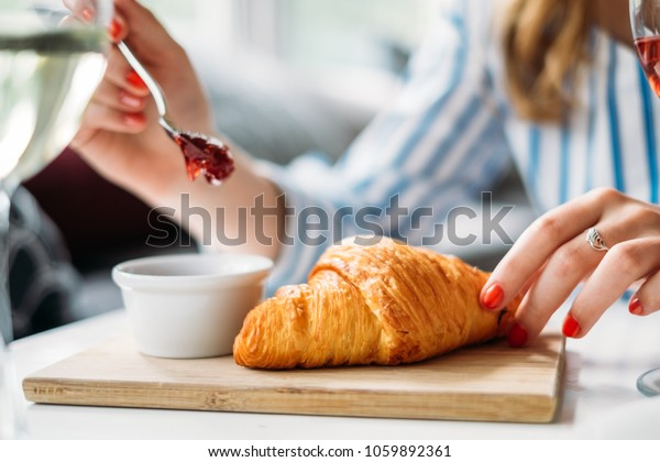 Woman ready to eat croissant with Strawberry jam