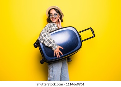 Woman ready for summer travel isolated on yellow background