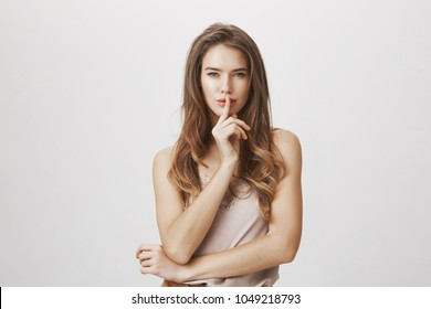 Woman ready to tell secret of beauty. Portrait of charming flirty caucasian female making shush or shh gesture with index finger over mouth, looking sensually and confident at camera over gray wall