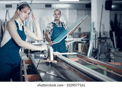 Woman is ready to working on circular saw on background with male assistant.