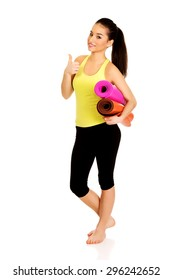 Woman ready for workout with yoga mats and thumbs up.