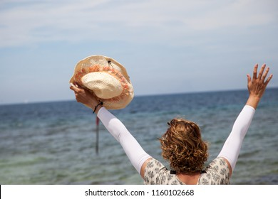 Woman in rear view with a hat in her hand waving her arms in front of the sea on a sunny day