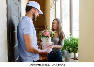 Woman received flowers, ordered by her boyfriend. Bearded deliveryman giving boxes with bouquets to her. Small business, local flower shop.