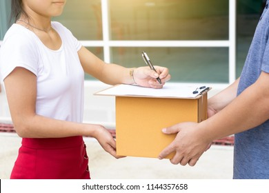 Woman received the parcel from the delivery worker. The loader man passes the boxes to the woman