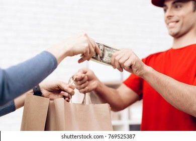 The woman received the parcel from the delivery worker. The woman pays the deliverer. A man in red clothes brought a package to a young woman. The woman pays for the man with cash.